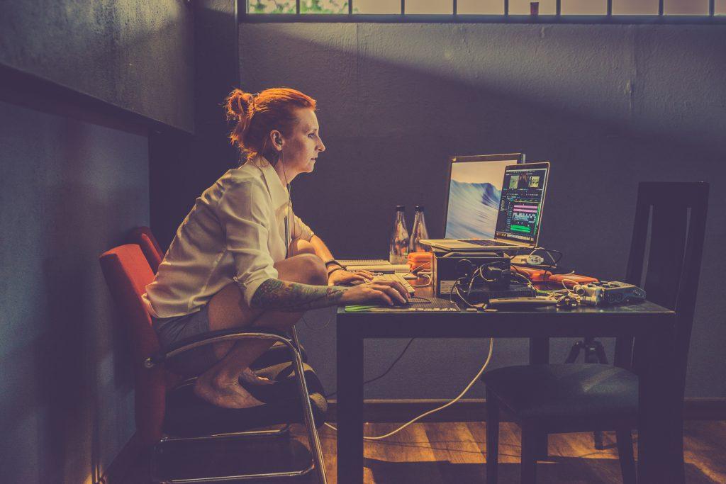 Sitter och arbetar framför datorn i ett mörkt rum