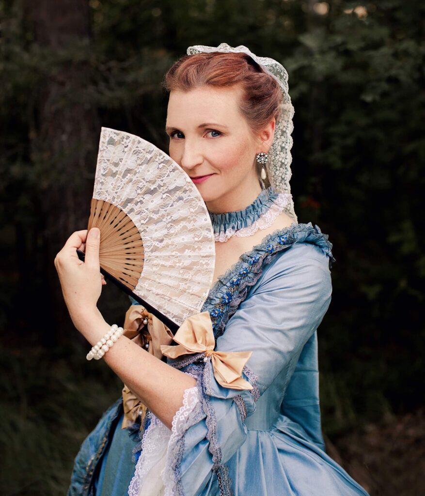 Viveka i blå 1700-tals klänning med solfjäder och fina smycken